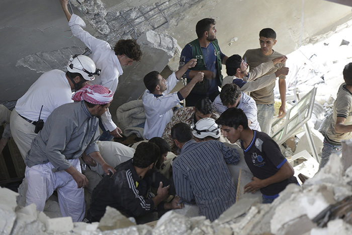 Civil defence members and civilians search for survivors under the rubble of a site hit by what activists said were cluster bombs dropped by Russian air force in Maasran town, south of Idlib, Syria October 7, 2015 (Reuters Photo)