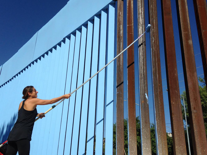 Artist Ana Fernandez paints the Sonora border fence blue as part of the art installation, ,Erasing the Border,, in Nogales, Mexico,Tuesday, Oct. 13, 2015. (AP Photo)