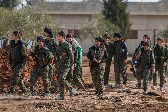 Kurdish female fighters of the YPG carry their weapons as they walk in the frontline of Kery Sabee village, northeastern Syria (AP Photo)