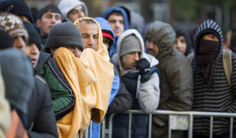 Refugees and migrants try to keep warm during temperatures around freezing as they wait to register and be allocated a sleeping place on the premises of the State Office of Health and Welfare (LaGeSo) in Berlin, Germany.