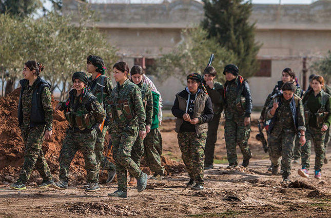 Kurdish female fighters of the YPG carry their weapons as they walk in the frontline of Kery Sabee village, northeastern Syria AP Photo
