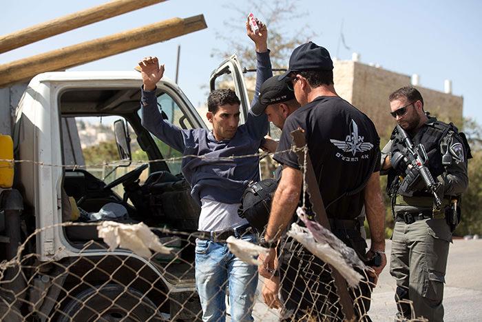 Israeli border policemen check a Palestinian driver on a road linking the Palestinian neighbourhood of Jabal Mukaber in East Jerusalem and Jerusalem on October 14, 2015 (AFP Photo)