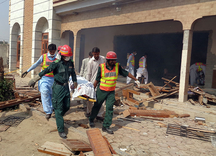 Pakistani rescuers move the body of a blast victim at the site of a suspected suicide bomb attack in Taunsa town, in Punjab province on October 14, 2015.