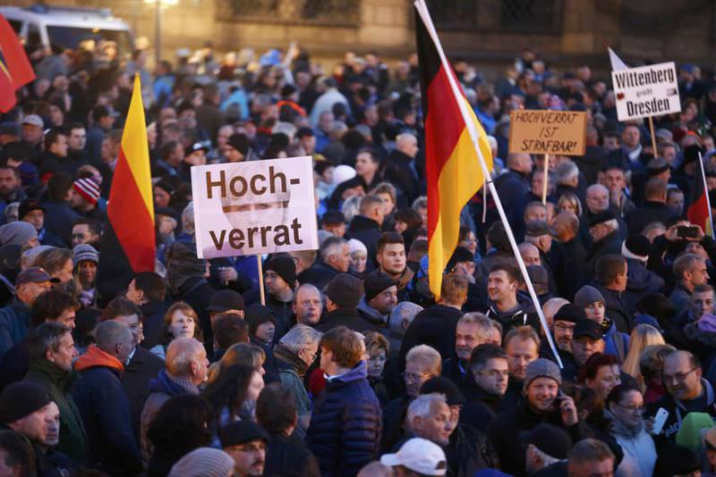 People hold up a sign reading 'high treason' as they gather for an anti-immigration demonstration organized by the extreme right movement PEGIDA in front of the Palace Church in Dresden.