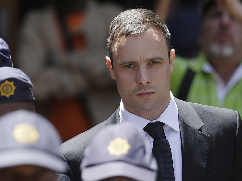 In this Friday, Oct. 17, 2014 file photo, Oscar Pistorius is escorted by police officers as he leaves the high court in Pretoria, South Africa (AP Photo)