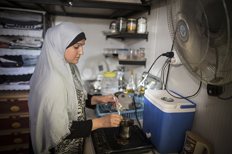 Syrian refugee woman who fled Syria, makes coffee at her prefabricated house at a tent city in the Harran District of u015eanlu0131urfa, Turkey on September 24, 2015 (AA photo).