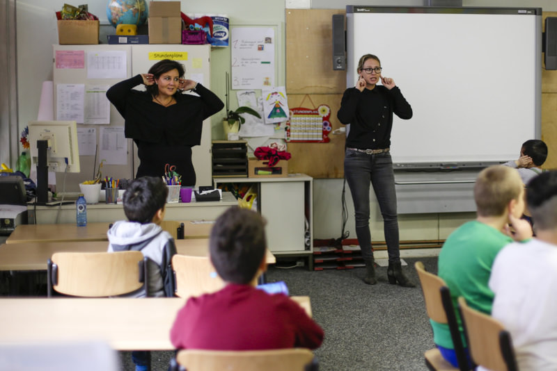 A volunteer (L) and teacher (R) teach students in a ,Willkommensklasse, (Welcome Class) at an elementary school at the Baeke in Berlin.