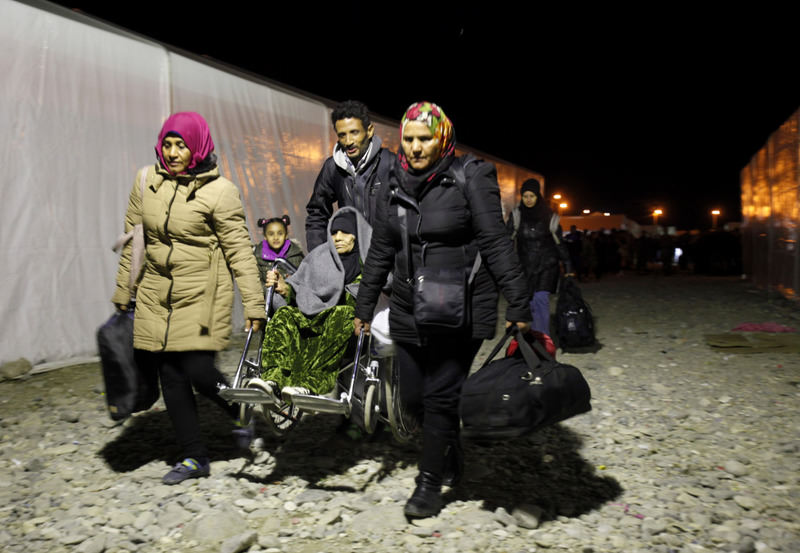 Syrian migrants help an elderly woman in a wheelchair at the transit camp for refugees near the southern Macedonian town of Gevgelija.