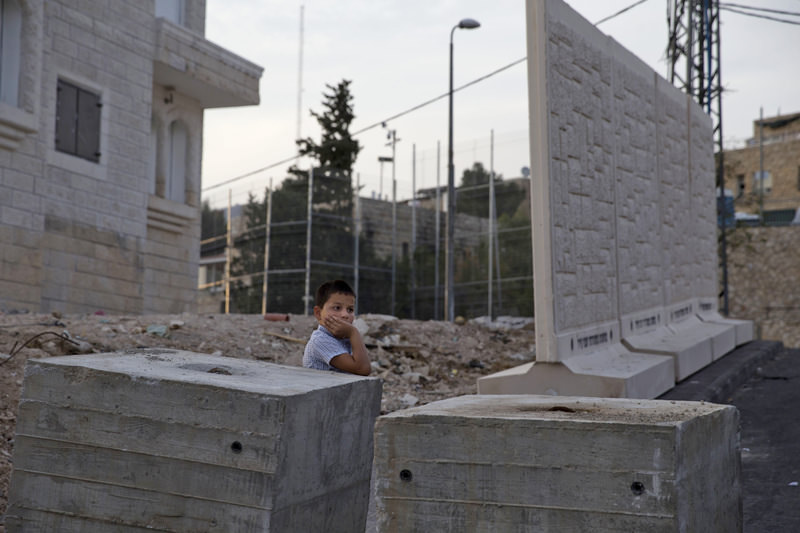 A Palestinian boy stands by concrete barrier between the Arab neighborhood of Jabal Mukaber and the Jewish area of Armon Hanatziv in east Jerusalem, Sunday, Oct. 18, 2015. (AP Photo)