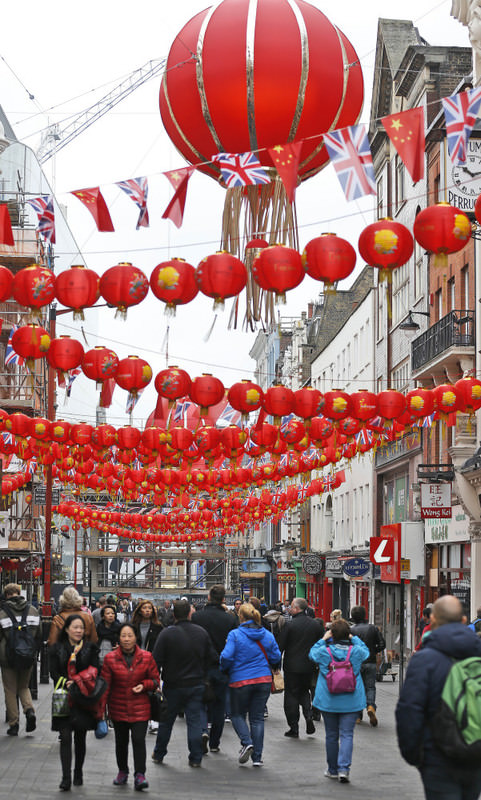 People walk through a decorated street in Chinatown in London. London is preparing for the visit of Chinese President Xi, accompanied by his wife Peng Liyuan, starting today.