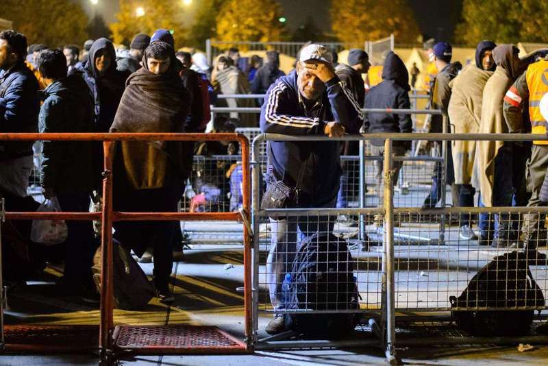 Refugees rest as they wait to board a bus before being transfered to Austrian refugee centers on the Austrian side of the border crossing between Sentilj (Slovenia) and Spielfeld on Oct. 17.