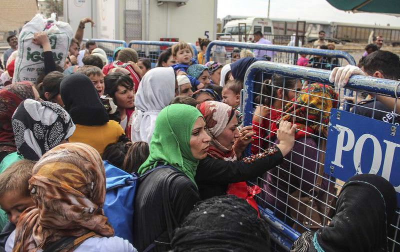 Syrians amassed at the border gate to cross into Syria. Every week, some 5,000 people travel to Kobane from Turkey.