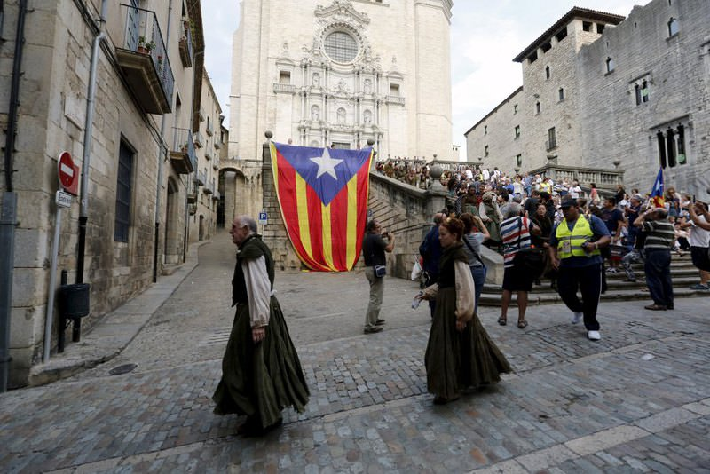 Extras make their way to Girona Cathedral, walking pass a Catalonia pro-independence flag while taking part in the filming for Season 6 of the HBO TV series ,Game of Thrones, in Girona, northeast of Spain.