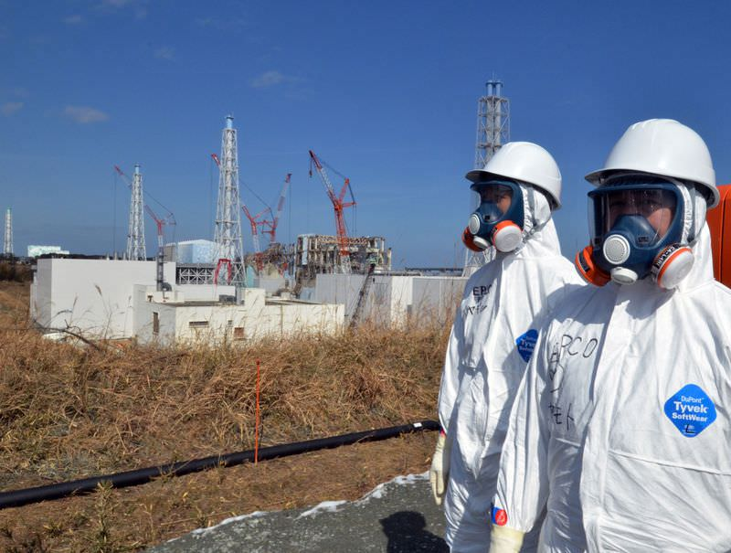 This file picture taken on February 28, 2012 shows Tokyo Electric Power Co (TEPCO) workers standing before the stricken Fukushima Dai-ichi nuclear power plant at Okuma town in Fukushima prefecture, northern Japan. (AFP Photo)