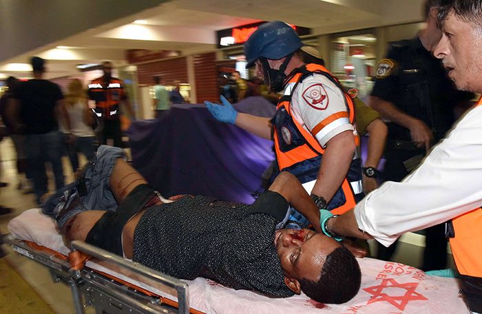 A wounded Eritrean man who later died of his wounds, is evacuated at the main bus station in the southern Israeli city of Beersheva on October 18, 2015 (AFP Photo)