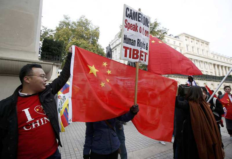 Supporters of China's President Xi Jinping and opponents hold flags and placards as they wait on the Mall for him to pass during his ceremonial welcome in London.