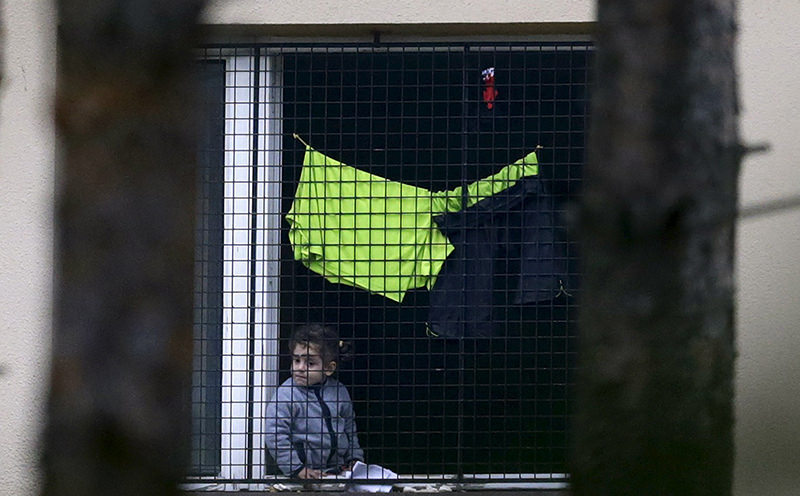A migrant child looks out of a window in the Facility For Detention Of Foreigners in Bela-Jezova, Czech Republic (Reuters Photo)