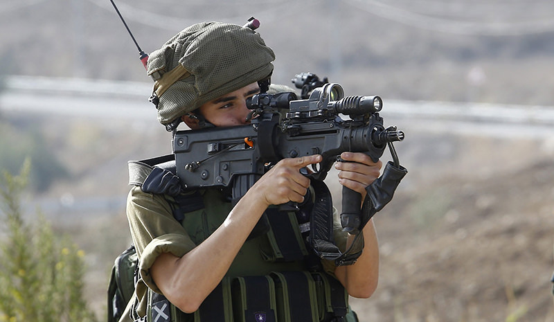 An Israeli soldier aims his gun at unarmed Palestinian protesters at the Howara checkpoint near the West Bank city of Nablus. (Photo EPA)