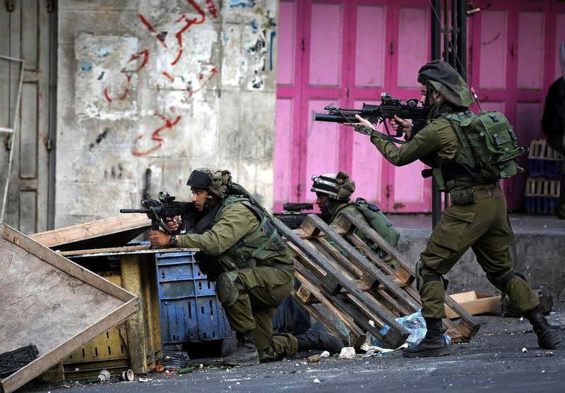 Israeli soldiers take up position during clashes with Palestinian protesters in the West Bank city of Hebron.