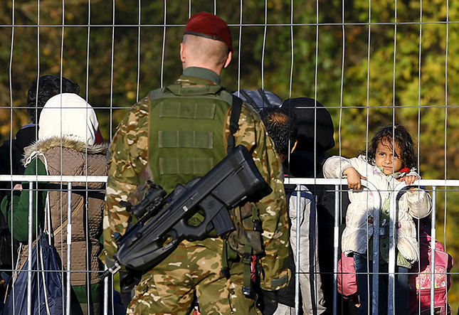A member of the Sowenian army observes migrants walking towards the Austrian border near the village of Sentilj, Slovenia, October 24, 2015. (Reuters Photo)