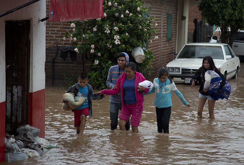 Residents walk along a flooded street in Zoatlan, Nayarit state, some 150 km northwest of Guadalajara, Mexico, Saturday, Oct. 24, 2015 (AP Photo)