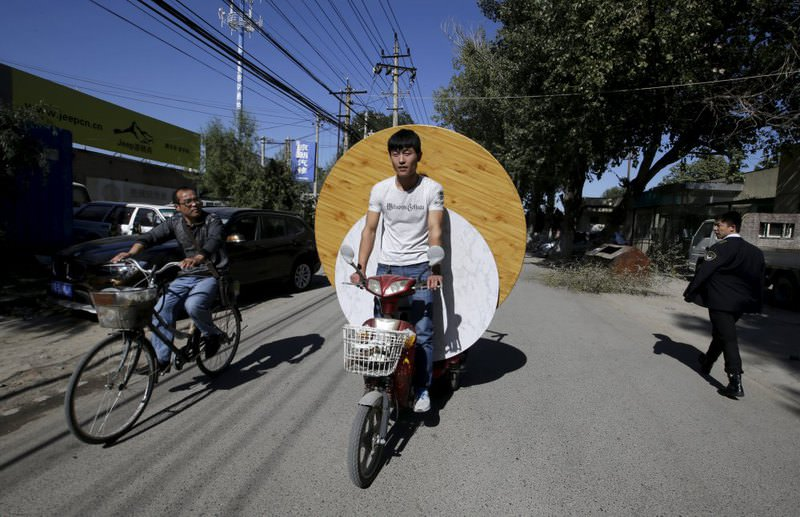 A man rides an electric bicycle carrying dining tables along a street inside a residential area for migrant workers on the outskirts of Beijing.