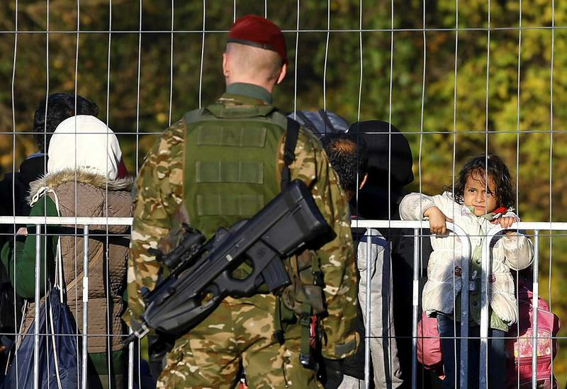 A member of the Slovenian army observes migrants walking towards the Austrian border near the village of Sentilj, Slovenia.