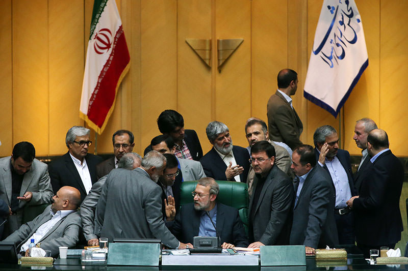 Iran's parliament speaker Ali Larijani (C) speaks with a member of parliament during a session in Tehran on October 11, 2015 (AFP photo)