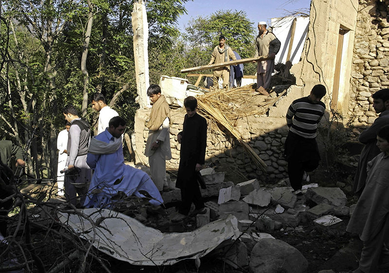 Pakistani residents gather among the rubble of houses following an earthquake in Lower Dir on October 27, 2015 (AFP Photo)