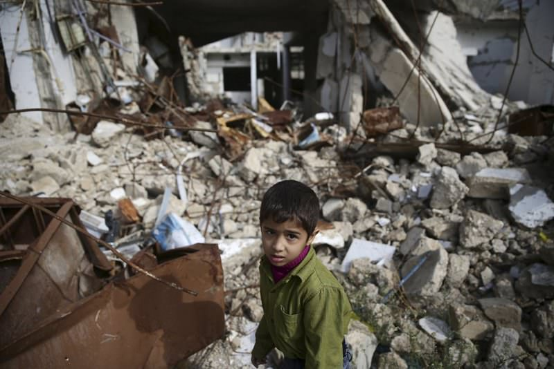 A boy walks amid buildings damaged by Russian airstrikes in the eastern Ghouta town of Douma in Damascus, Syria.