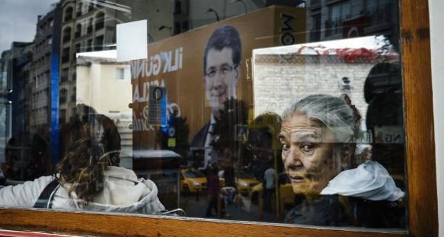 A woman looks out a tram window that is reflecting a banner of Turkish Prime Minister Ahmet Davutoglu on Oct. 30 in Istanbul.emAFP Photo/em