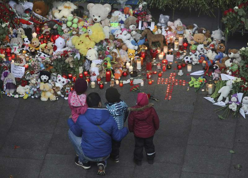 A man and children mourn near a makeshift memorial for victims of a Russian airliner that crashed in Egypt, outside Pulkovo airport in St. Petersburg.