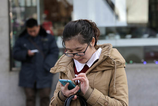 Chinese people use their smartphones on a street in Beijing Monday, Feb. 16, 2015. (Associated Press)
