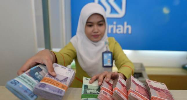An employee of BRI Syariah bank manages bundles of Indonesian rupiah bank notes in Jakarta.