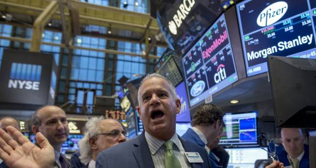 Traders gather as New York Stock Exchange (NYSE) Floor official Rudy Mass (C) opens Pfizer's stock on the floor of the NYSE on Friday.