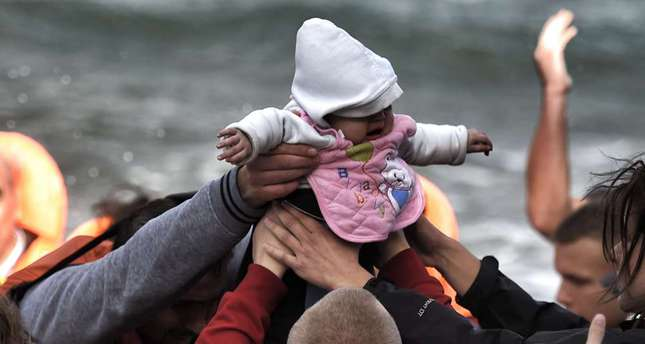 A baby is carried by migrants as they arrive on the Greek island of Lesbos after crossing the Aegean Sea from Turkey.