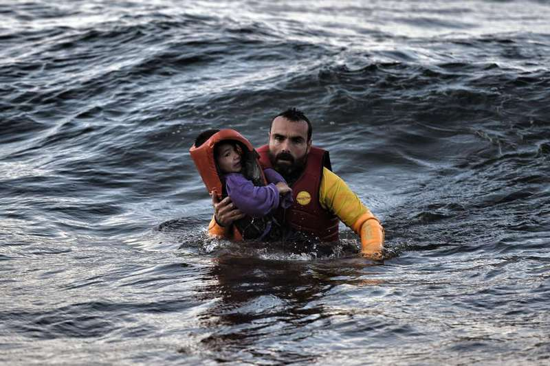 A Spanish lifeguard rescues a child as a boat with refugees sunk on Oct. 30.