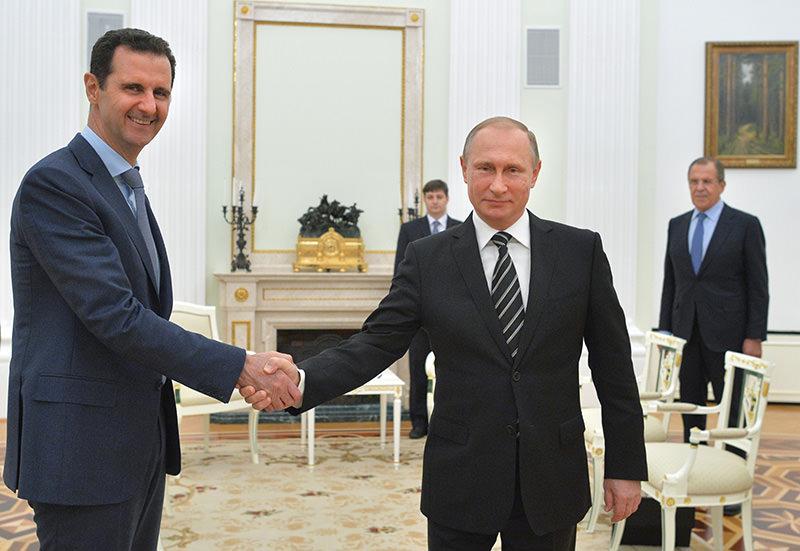 Russian President Vladimir Putin, center, shakes hand with Syrian President Bashar Assad as Russian FM Sergey Lavrov, right, looks on in the Kremlin (AP photo)