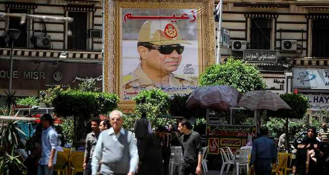 Egyptians walk past a poster bearing a portrait of retired army chief and current President AbdelFattah el-Sissi.