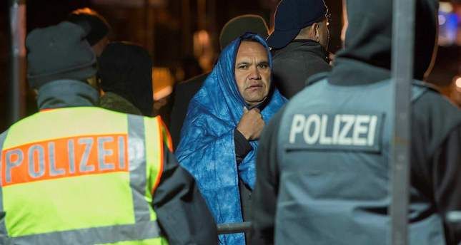 An Afghan refugee wrapped in a blue blanket to protect himself against the cold waits to cross into Germany.