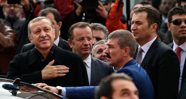 Erdoğan gestures to supporters after casting his ballot for the elections at a polling station in Istanbul