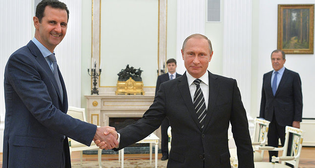 Russian President Vladimir Putin, center, shakes hand with Syrian President Bashar Assad as Russian FM Sergey Lavrov, right, looks on in the Kremlin AP photo