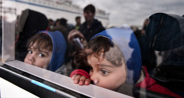 Refugee children peek out from a bus taking them to the city's center, after disembarking from a government chartered ferry at the port of Piraeus on October 30, 2015. (AFP Photo)