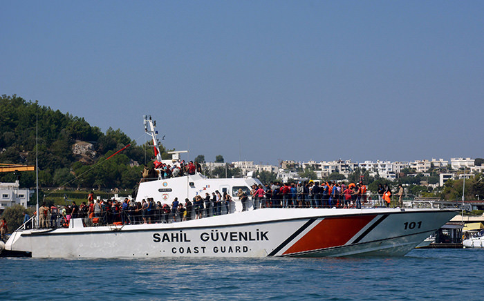 Refugees rescued from a capsized boat wait to disembark from a Coast Guard ship in the resort town of Bodrum, in Mugla province September 15, 2015 (Reuters Photo)
