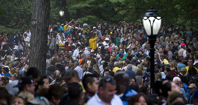 People in a large crowd reach out to get photographs as Pope Francis passing while traveling in a motorcade in New York's Central Park, Friday, Sept. 25, 2015. (AP Photo)