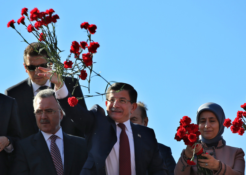 PM Davutou011flu throws carnations to his supporters at Atatu00fcrk Airport, following the AK Party's election victory.