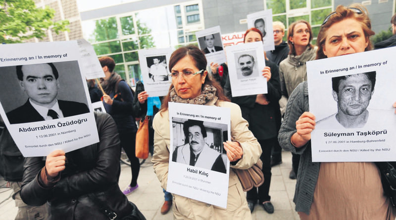 Protesters hold photos of NSU's victims outside a courthouse in Munich where Beate Zschaepe, the sole surviving member of the gang, stands trial.