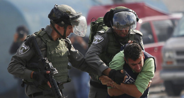 Israeli police wrestle a Palestinian cameraman during clashes outside Ramallah, West Bank.