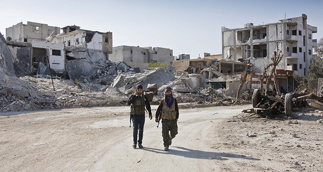 YPG soldiers walk near the town entrance circle heading to their strongholds in Kobani, Syria (AP Photo)