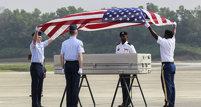 US military honor guards cover with the US flag a coffin containing human remains recoved from the crash in Subang, Malaysia (EPA Photo)